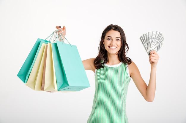 Retrato de una niña satisfecha en vestido con bolsas de compras