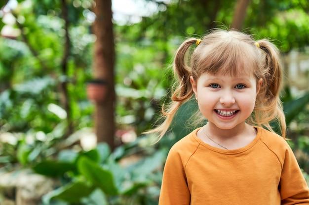 Retrato de una niña en la selva. niño alegre en el zoológico.