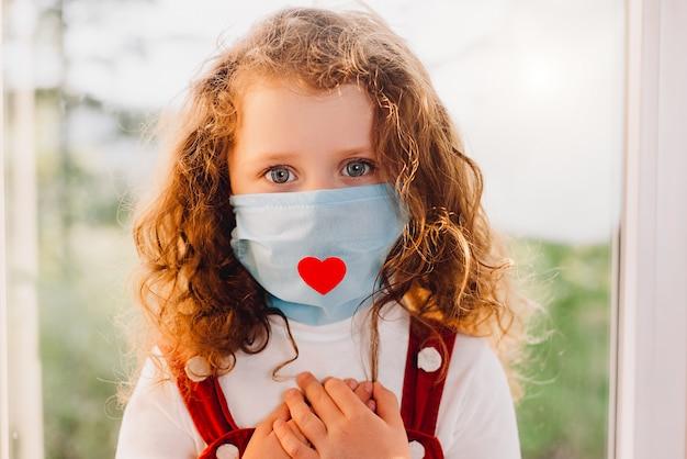 Retrato de niña sentada en el alféizar de la ventana con una máscara de salud con un corazón rojo como una forma de mostrar agradecimiento y agradecer a todos los empleados esenciales durante la pandemia de covid-19