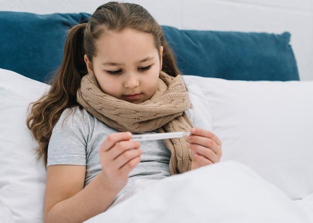 Retrato de una niña sentada en la cama con una bufanda alrededor del cuello mirando termómetro