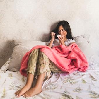 Retrato de una niña sentada en la cama tomando café