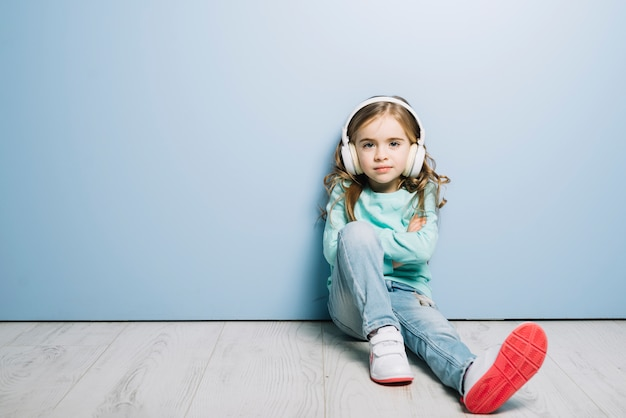 Retrato de una niña sentada contra azul con auriculares en su cabeza escuchando música