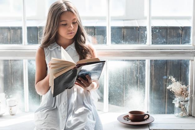 Retrato de una niña sentada junto a la ventana leyendo un libro