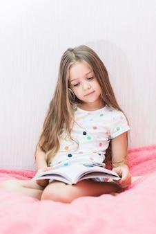 Retrato de una niña sentada en el libro de lectura de cama de color rosa suave