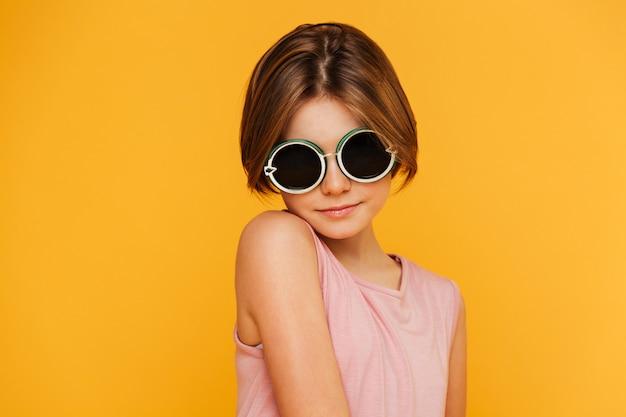 Retrato de niña seria en gafas de sol mirando a la cámara