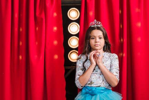 Retrato de niña seria de pie delante de la cortina roja con luz de la etapa