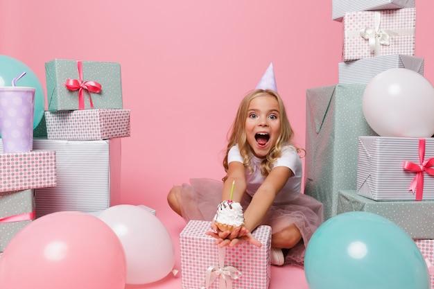Retrato de una niña en un sombrero de cumpleaños celebrando