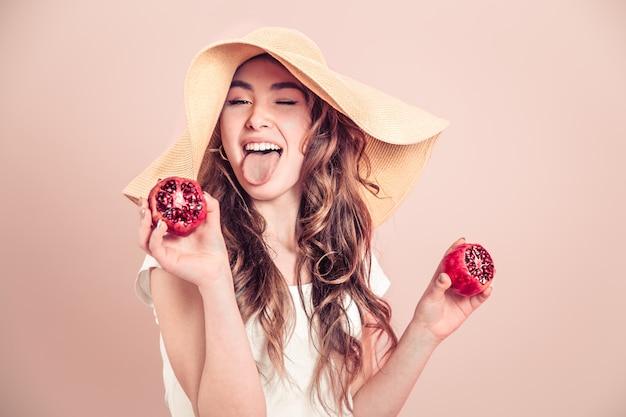 Retrato de una niña en un sombrero de verano con fruta en una pared de color