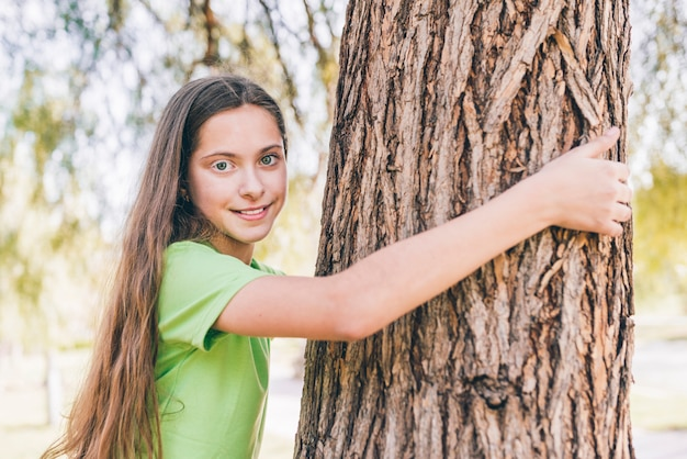 Retrato de una niña sonriente abrazando el tronco de un árbol