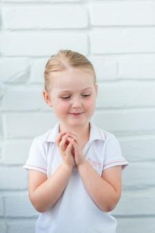 Retrato de niña sonriente alegre en un espacio de pared blanca