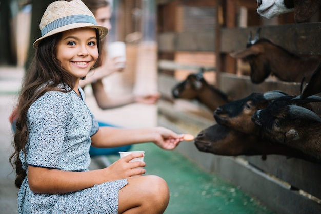 Retrato de niña sonriente alimentación galleta a cabra en el granero
