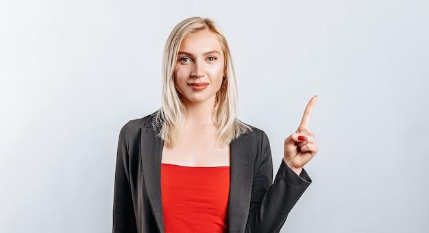 Retrato de una niña sonriente apuntando con el dedo hacia arriba en copyspace aislado sobre fondo blanco. una mujer señala una idea, un lugar de publicidad. rubia positiva.