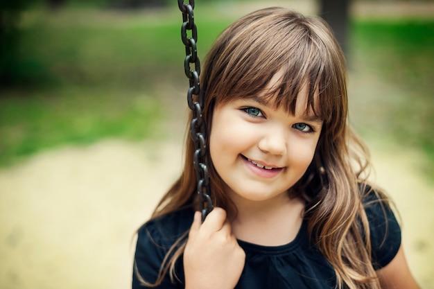 Retrato de niña sonriente en columpio