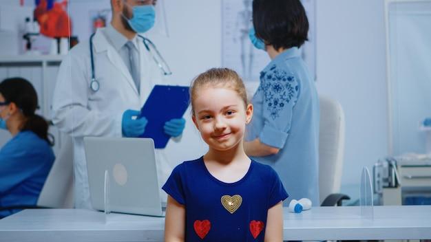 Retrato de niña sonriente en consultorio médico mientras la madre habla con el médico en segundo plano. especialista en medicina con máscara de protección que brinda servicios de atención médica, consulta en clínica hospitalaria