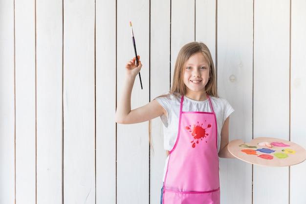 Retrato de una niña sonriente en delantal con pincel y paleta de madera en la mano contra la pared de tablones de madera