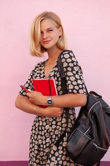 Retrato de niña sonriente estudiante de moda con mochila negra y sosteniendo lácteos rojos