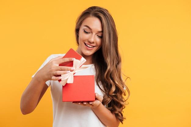 Retrato de una niña sonriente feliz abriendo la caja de regalo