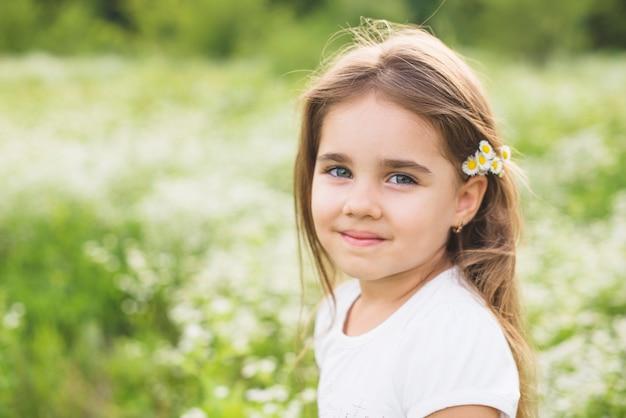 Retrato de niña sonriente con flores en la cabeza