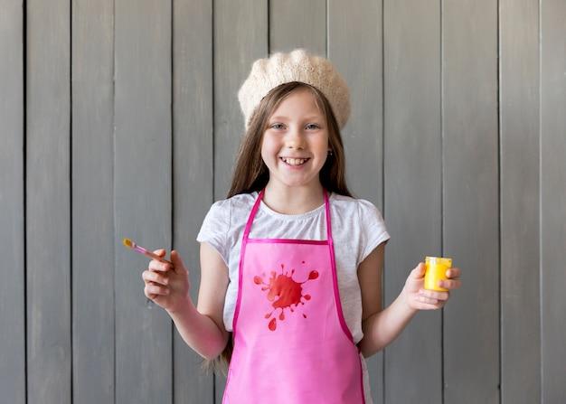 Retrato de una niña sonriente con una gorra de punto que sostiene un pincel y una botella de pintura amarilla en las manos