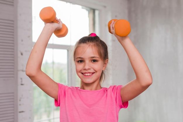 Retrato de una niña sonriente haciendo ejercicio con una pesa de gimnasia naranja