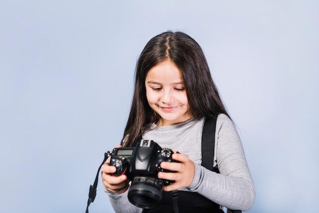 Retrato de una niña sonriente mirando a la cámara contra el telón de fondo azul