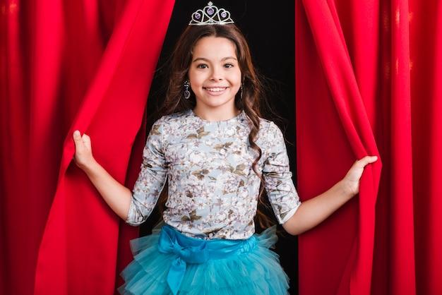 Retrato de niña sonriente mirando desde la cortina roja