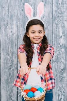 Retrato de una niña sonriente con orejas de conejo que ofrece la canasta de huevos de pascua
