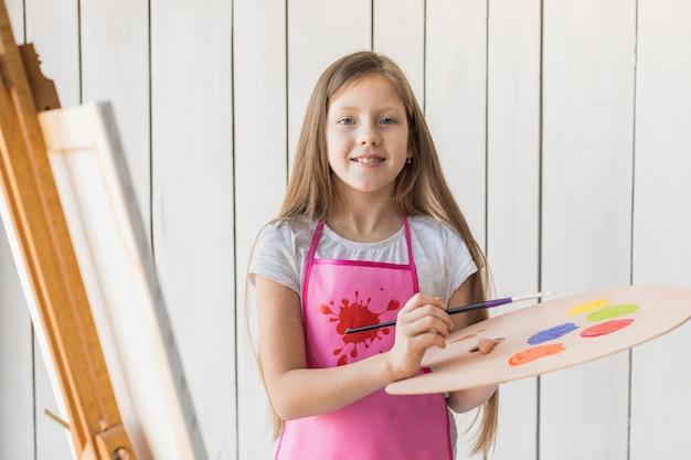 Retrato de una niña sonriente con paleta de madera y pincel de pie contra la pared de madera blanca
