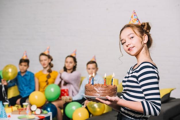 Retrato de una niña sonriente con pastel de cumpleaños con amigos en el fondo