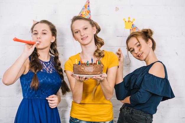 Retrato de una niña sonriente con pastel de cumpleaños de pie con sus amigos
