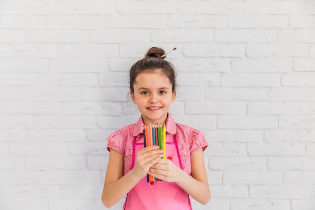 Retrato de una niña sonriente de pie contra la pared de ladrillo blanco con lápices de colores en la mano