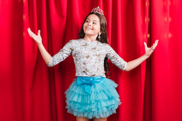 Retrato de una niña sonriente de pie detrás de la cortina roja encogiéndose de hombros