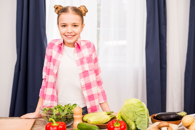 Retrato de una niña sonriente de pie detrás de la mesa con verduras frescas