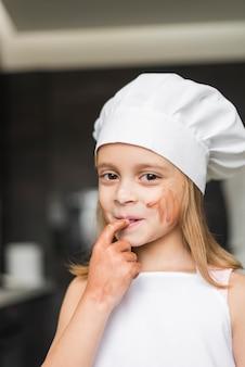 Retrato de niña sonriente poniendo su dedo en la boca