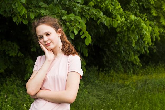 Retrato de niña sonriente posando en el parque