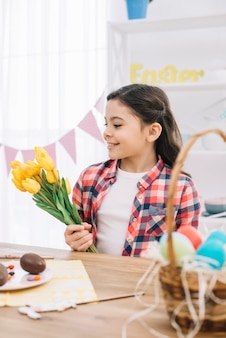 El retrato de una niña sonriente que sostiene el tulipán amarillo florece el día de pascua