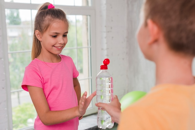 Retrato de una niña sonriente recibiendo botella de agua de su amiga