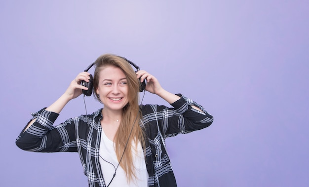 Retrato de una niña sonriente en ropa casual de pie sobre un fondo púrpura, escuchando música y mirando a otro lado. chica con auriculares aislados sobre fondo morado mira copyspace