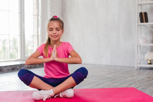 Retrato de una niña sonriente sentada en la alfombra rosada con la pierna cruzada meditando