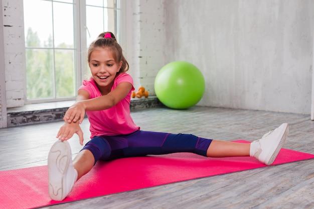 Retrato de una niña sonriente sentada en una estera de ejercicios estirando su mano y pierna
