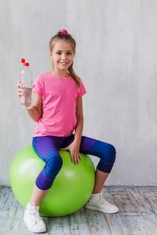 Retrato de una niña sonriente sentada en pilates verde sosteniendo una botella plástica de agua en la mano
