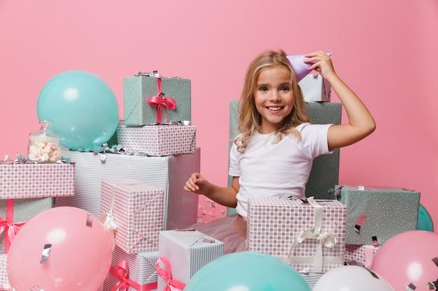 Retrato de una niña sonriente en un sombrero de cumpleaños celebrando