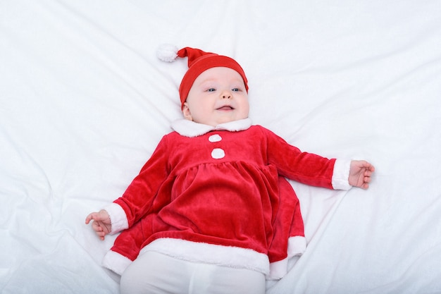 Retrato de niña sonriente en un sombrero de santa y un vestido rojo. concepto de navidad