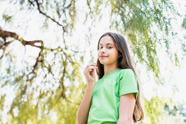 Retrato de una niña sonriente sosteniendo un helecho en la mano mirando a la cámara de pie debajo del árbol