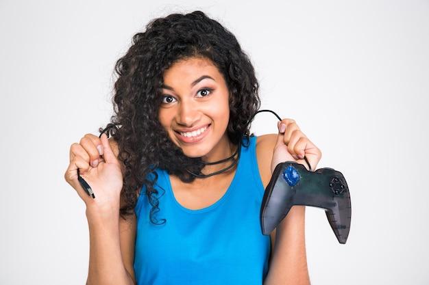 Retrato de una niña sonriente sosteniendo el joystick de juegos aislado en una pared blanca