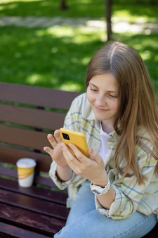 Retrato de niña sonriente con un teléfono inteligente en sus manos en un banco del parque concepto personas y gadgets