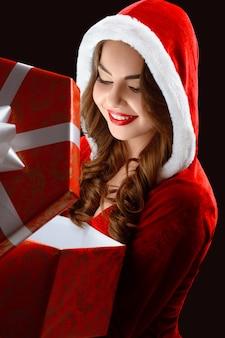 Retrato de niña sonriente en el traje rojo, abriendo un regalo para año nuevo