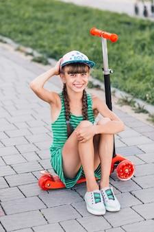 Retrato de una niña sonriente vistiendo gorra sentado en scooter de empuje rojo