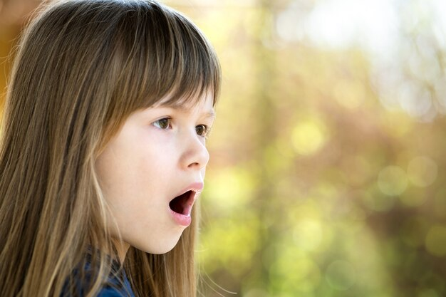 Retrato de niña sorprendida al aire libre en verano. cabrito sorprendido en un día caluroso afuera.
