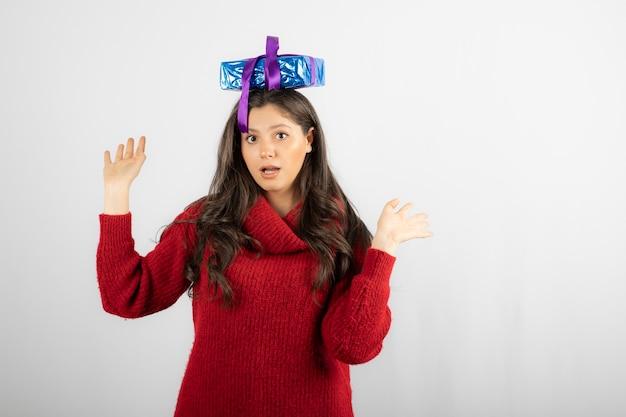 Retrato de una niña sorprendida poniendo una caja de regalo en la cabeza.